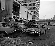 Car Bomb Damage in Dublin (E10)..1972.02.12.1972..12.02.1972..2nd December 1972..On the morning of 2nd December '72 two car bombs exploded in Dublin City. At Sackville Place two busmen were killed as they waited in their car to resume work. The busmen were named as George Bradshaw (30) and Thomas Duffy (23). The bomb was thought to be planted by a Northern Ireland subversive group who hoped to influence legislation going through Dail Eireann in relation to the I.R.A...Picture of the devastation caused by the bomb explosion on Eden Quay. A group of parked cars lie devestated along the footpath.