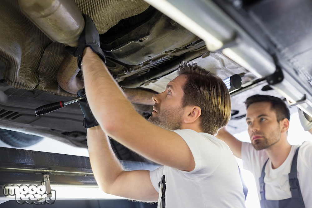 Male repair workers examining car in workshop