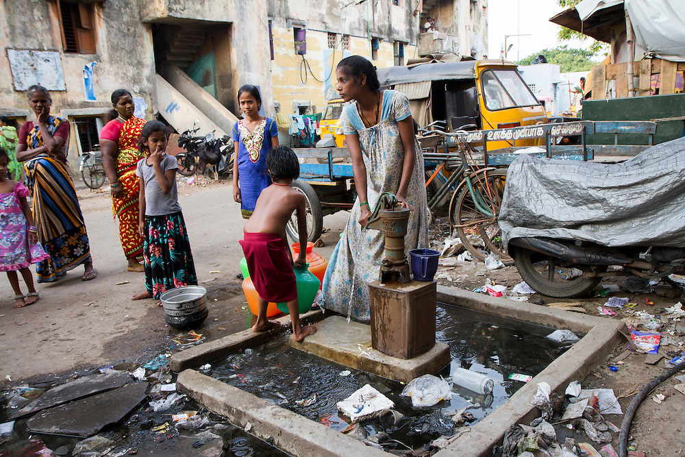 A young woman fills containers of water in a slum in Chennai, India, one of 40 that Janodayam works with.  The water is contaminated with raw sewage due to broken pipes and flooding.