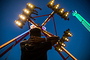 WASHINGTON, USA - August 19: A boy watches as one of the brightly lit amusement rides swings over his head high into the sky at the Montgomery County Agricultural Fair in Gaithersburg, Md., USA on August 19, 2017.