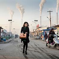 China, Shanxi Province, Datong, Young woman walks through gritty neighborhood streets beneath smokestacks at Datong No. 2 Power Station at dawn