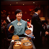 Waitress Florence LIang with a dim sum cart at the restaurant Sun Sui Wah in Vancouver, British Columbia, Canada.  Dim sum is the name for a Chinese Cuisine which involves a wide range of light dishes served along Chinese tea.
