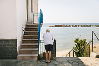ACCIAROLI, ITALY - 14 SEPTEMBER 2018: An elderly man looks at the beach and the sea in Acciaroli, a small fishing village in the municipality of Pollica, Italy, on September 14th 2018.<br /> <br /> To understand how people can live longer throughout the world, researchers at University of California, San Diego School of Medicine have teamed up with colleagues at University of Rome La Sapienza to study a group of 300 citizens, all over 100 years old, living in Acciaroli (Pollica), a remote Italian village nestled between the ocean and mountains in Cilento, southern Italy.<br /> <br /> About 1-in-60 of the area's inhabitants are older than 90, according to the researchers. Such a concentration rivals that of other so-called blue zones, like Sardinia and Okinawa, which have unusually large percentages of very old people. In the 2010 census, about 1-in-163 Americans were 90 or older.