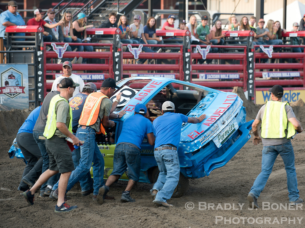 Crews right an overturned racer's car during the second heat of the 2017 Figure 8 Races on Sunday at the Teton County Fair.