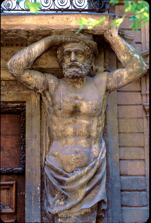 Male caryatid on the facade of a bank in Aix-en-Provence.  Bearded face, bare chested, wearing a wrap around his hips.