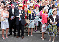 © licensed to London News Pictures. LONDON, UK.  28/07/11. Crowds watch a race.  Ladies day at Glorious Goodwood on 28 July 2011. More than 100,000 people flock through the gates of Glorious Goodwood to enjoy the atmosphere. There are racing highlights every day - including the Sussex Stakes, the Goodwood Cup and the Markel International Nassau Stakes.Mandatory Credit Stephen Simpson/LNP