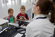 "A young brother and sister look on in awe while a British Airways check-in lady asks security questions of the pair's parents who are taking her children on a long-haul flight from London Heathrow Airport's Terminal 5. The family baggage has been tagged and is about to disappear down the belt to join up to 70,000 other items in this average day at T5. The siblings stare as the young woman checks the travel details of the mother and father who have booked Business Class seats for them all. From writer Alain de Botton's book project ""A Week at the Airport: A Heathrow Diary"" (2009). ."