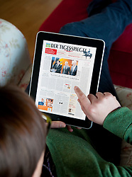 Woman using iPad tablet computer to read German daily newspaper Der Tagesspiegel