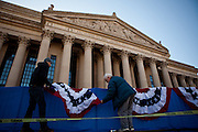 Travon Bristol, left, and Ken Hines hang bunting in front of the National Archives for the presidential inaugural parade, January 20, 2013 in Washington, D.C.