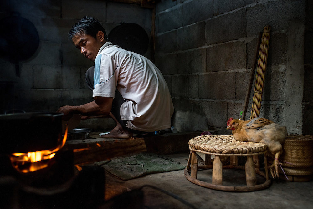 A man washes cooking pots before preparing a chicken for dinner in the village of Khoc Kham.