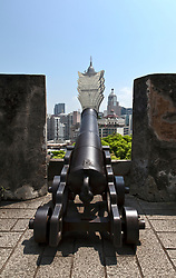 An old canon at the Fortaleza do Monte seems aimed directly at the Grand Lisboa Hotel, a distinctive feature of the Macau skyline, China.  The old fort is part of Macau's Historical Centre, in itself a UNESCO World Heritage Site.