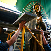 Daniel Zeferino removes scaffolding from around a 12 foot-tall, 4,000 pound statue of Our Lady of Guadalupe at a foundry in Mexico City. The statue was commissioned by the historic Our Lady of Guadalupe church in Santa Fe, New Mexico. The statue was commissioned and funds raised after a controversial state-sponsored art exhibit that pushed the boundaries of the sacred and traditional image of Our Lady of Guadalupe. The statue was loaded onto a flatbed truck and driven north, following El Camino Real, the ancient route the Spanish settlers took north to settle New Mexico and the RIo Grande valley.