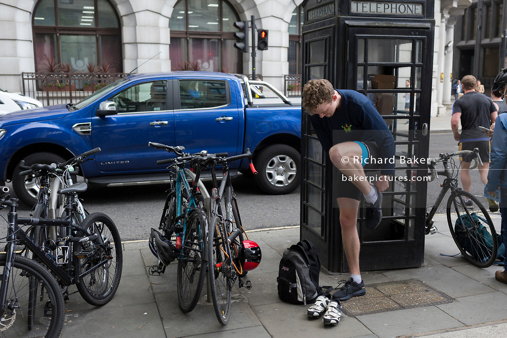 After locking his bike to a secure bar, a cyclist changes footwear next to a phone box in the City of London, the capital's financial district, on 25th April 2019, in the City of London, England.