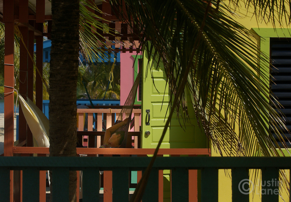A woman is seen sleeping in a hammock among multi-colored beach houses in Placencia, Belize, a beach town in the southern part of the country.<br />JUSTIN LANE FOR THE NEW YORK TIMES