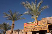 A old advert for Kodak film and palm tree inside the enclosure of the ancient Egyptian remains of Karnak in modern Luxor, Nile Valley, Egypt.