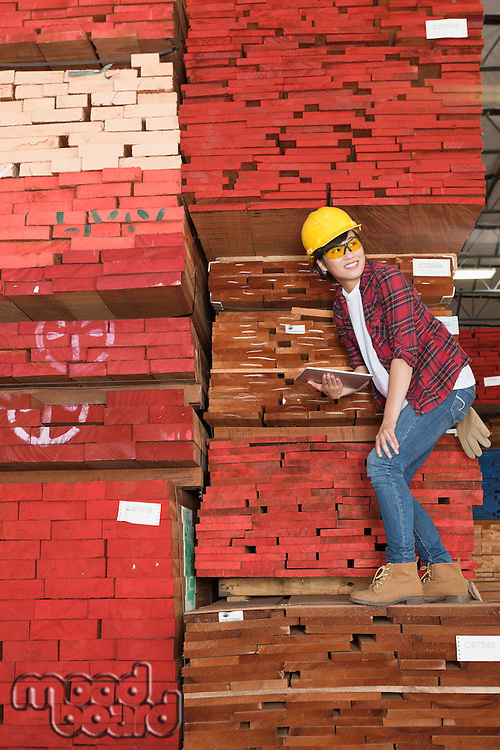 Asian female industrial worker standing on stacked wooden planks holding tablet PC