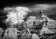 Most of the rainfall in the Badlands region falls in the period from May to July, often in the form of powerful storms, sometimes loosely referred to as monsoons. If the storms occur at sunrise or sunset, the light on this harsh and unusual landscape can be dramatic. Badlands National Park in South Dakota, USA.