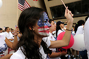 Student Elizabeth Bento holds an American flag while she listens to speakers in front of Dallas City hall during the MegaMarch for Immigration Reform, May 01, 2010