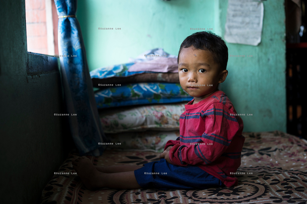 Sujal Tamang (2) sits on a bed for a portrait in his aunt's rented apartment in Jorpati, Kathmandu, Nepal on 2 July 2015. Sujal was buried under the rubble of his collapsed house for 36 hours before rescuers found him injured with a broken leg next to his mother who was killed on the spot. Photo by Suzanne Lee for SOS Children's Villages