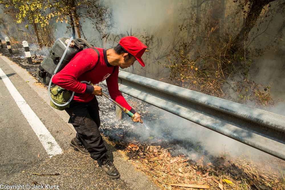 "06 APRIL 2013 - CHIANG MAI, CHIANG MAI, THAILAND: Thai firefighters work to control an illegal burn that got out of control on a hillside on the edge of Chiang Mai. The ""burning season,"" which roughly goes from late February to late April, is when farmers in northern Thailand burn the dead grass and last year's stubble out of their fields. The burning creates clouds of smoke that causes breathing problems, reduces visibility and contributes to global warming. The Thai government has banned the burning and is making an effort to control it, but the farmers think it replenishes their soil (they use the ash as fertilizer) and it's cheaper than ploughing the weeds under.   PHOTO BY JACK KURTZ"