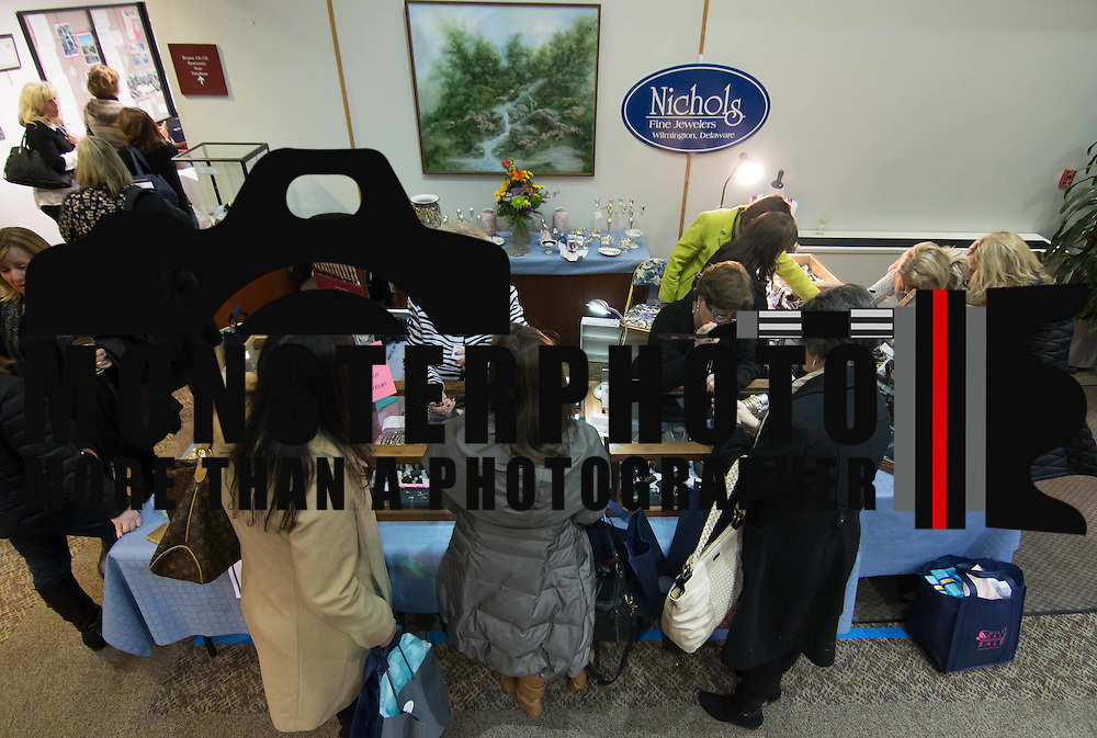 Shoppers browse though jewelry at the Nichols Fine Jewelers booth during the 3rd Annual Guilty Girls Warehouse Sale Friday, Feb. 06, 2015 at University of Delaware's Arsht Hall in Wilmington, DE.