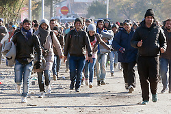 Licensed to London News Pictures. 03/11/2015. Sentilj, Slovenia. Migrants are running to the border crossing in Sentilj, Slovenia to enter Austria. Photo: Marko Vanovsek/LNP