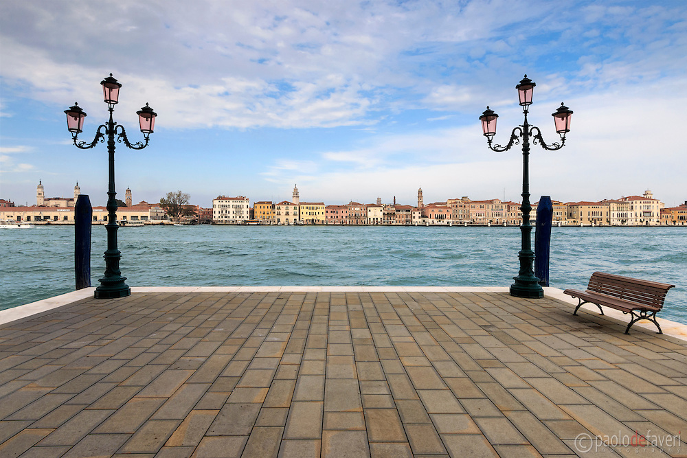 A very typical Venetian view, a simple, geometrical composition: a quay, a bench and two lamp posts on the Giudecca, and the strip of buildings of downtown Venice in the background.