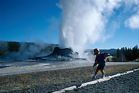 A boy walks in front of Castle Geyser, Yellowstone National Park, WY