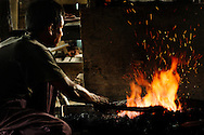 Blacksmith heating a piece of metal at a traditional workshop