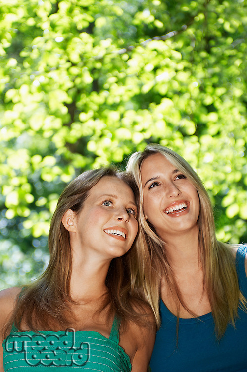 Two young women standing in forest looking up front view