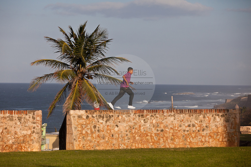 A young boy run along the old fortress wall of San Juan, Puerto Rico.