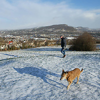 A man takes his dog for a walk on Craigie Hill overlooking Perth. The predicted bad weather has avoided the area with only a light dusting of snow. Pictured right is the Friarton Bridge and the hill picture centre is Kinnoull Hill.<br />