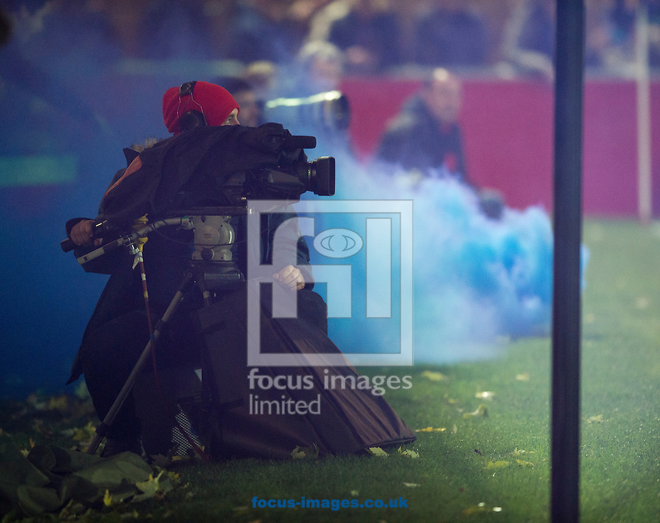 A TV camera operator is photographed against the background of a blue smoke bomb thrown from the Chesterfield fans' end during the FA Cup match at Broadhurst Park, Moston<br /> Picture by Russell Hart/Focus Images Ltd 07791 688 420<br /> 09/11/2015
