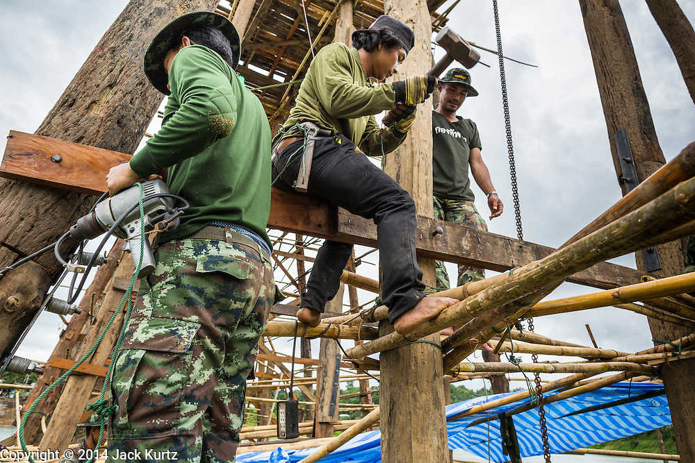 17 SEPTEMBER 2014 - SANGKHLA BURI, KANCHANABURI, THAILAND: Thai soldiers and members of the Mon community work at water level on the Mon Bridge. The 2800 foot long (850 meters) Saphan Mon (Mon Bridge) spans the Song Kalia River. It is reportedly second longest wooden bridge in the world. The bridge was severely damaged during heavy rainfall in July 2013 when its 230 foot middle section  (70 meters) collapsed during flooding. Officially known as Uttamanusorn Bridge, the bridge has been used by people in Sangkhla Buri (also known as Sangkhlaburi) for 20 years. The bridge was was conceived by Luang Pho Uttama, the late abbot of of Wat Wang Wiwekaram, and was built by hand by Mon refugees from Myanmar (then Burma). The wooden bridge is one of the leading tourist attractions in Kanchanaburi province. The loss of the bridge has hurt the economy of the Mon community opposite Sangkhla Buri. The repair has taken far longer than expected. Thai Prime Minister General Prayuth Chan-ocha ordered an engineer unit of the Royal Thai Army to help the local Mon population repair the bridge. Local people said they hope the bridge is repaired by the end November, which is when the tourist season starts.    PHOTO BY JACK KURTZ