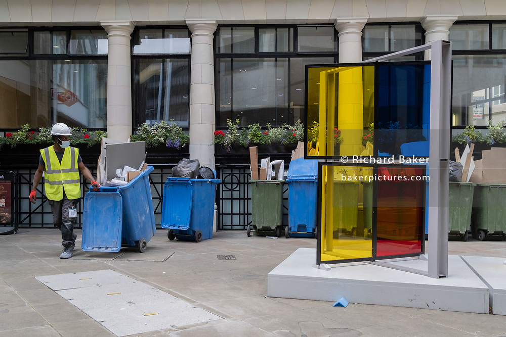 A City of London workman clears construction debris collected in bins, next to the artwork entitled 'Series Industrial Windows I' by Marisa Ferreira, part of Sculpture in the City 2019, on 6th August 2020, in London, England.