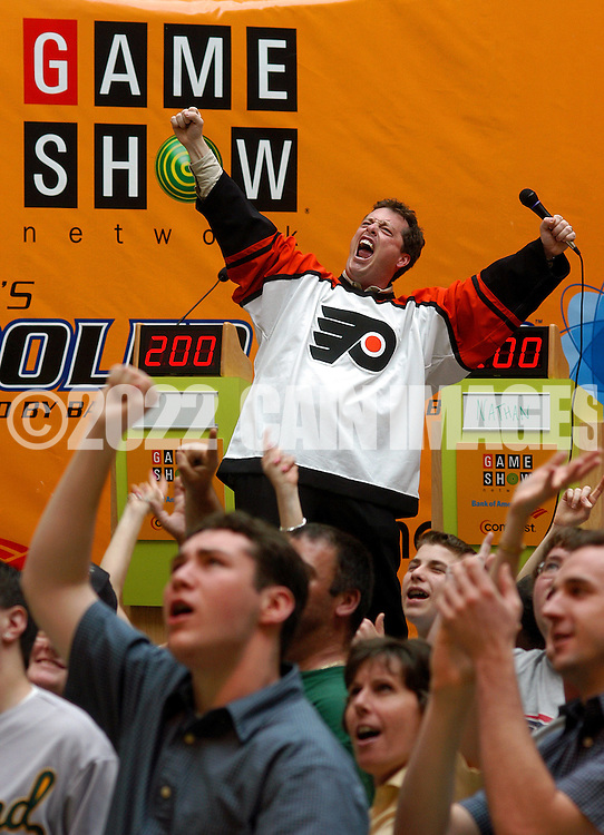 """KING OF PRUSSIA, PA.- MAY 31:  Todd Newton, host of the Game Show Network's """"Whammy"""" wears a Philadelphia Flyers jersey, cheers as he tapes a commercial promoting the Game Show Network, during the Game Show Network's """"Get Schooled Tour"""" at the King of Prussia Mall May 31, 2003 in King of Prussia, Pennsylvania. Ninety people competed in a live game show to win $10,000 towards college tuition. (Photo by William Thomas Cain/Game Show Network via Getty Images)"""