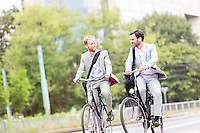 Businessmen talking while cycling outdoors