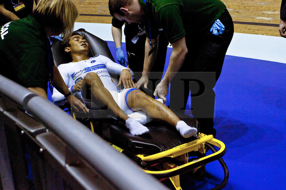 © Licensed to London News Pictures. 19/02/2011. UCI Track Cycling World Cup at Manchester Azizulhasni Awang is taken away on a stretcher after crashing during the final of the men's keirin. He had a splinter through his leg. But finished the race to take Bronze...A major crash on the final bend of the Men's Keirin, Final left a number of injuries. The worst appeared to be a splinter which penetrated right through the leg of the Malaysian rider Azizulhasni Awang. Photo credit should read: Reuben Tabner/LNP