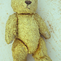 Well-worn yellow fur vintage teddy bear with flattened ears and sad expression lying on antique paper