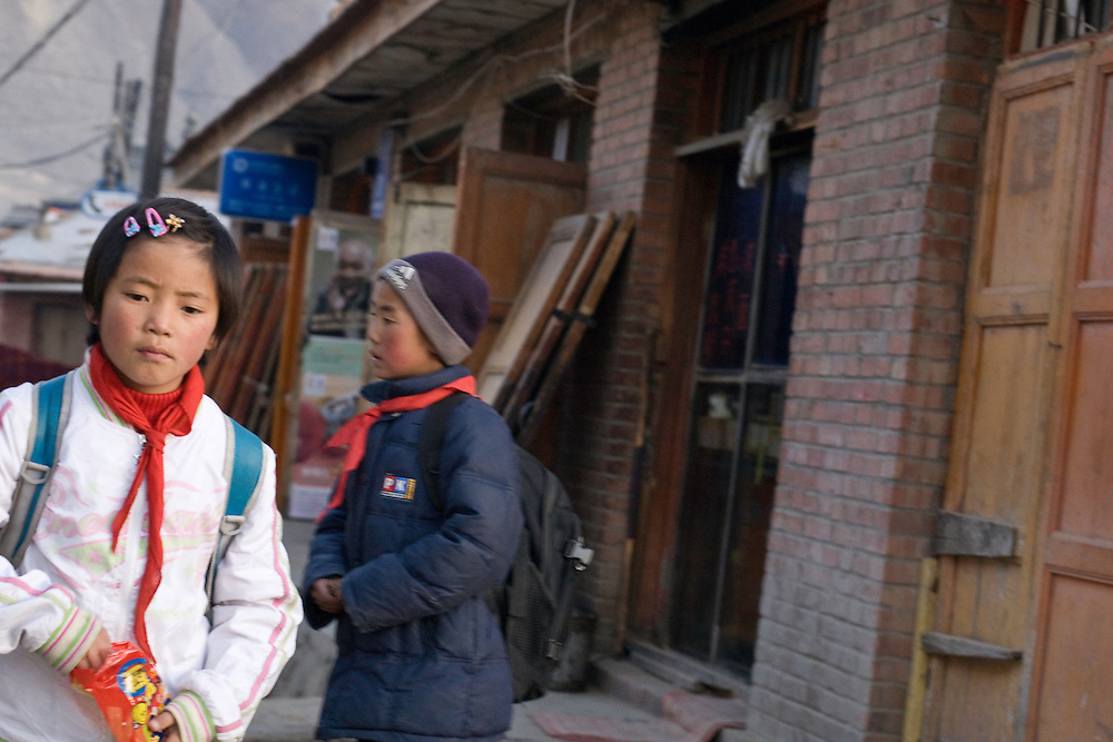 """Children going back to home after the school, in the tibetan part of Xiahe. They wear the red scarf of the communist """"Pionners""""."""