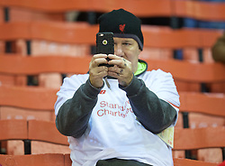 LIVERPOOL, ENGLAND - Thursday, November 26, 2015: A Liverpool supporter takes a photo on an Apple iPhone before the UEFA Europa League Group Stage Group B match against FC Girondins de Bordeaux at Anfield. (Pic by David Rawcliffe/Propaganda)