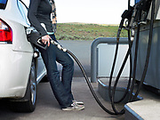 30's something woman leaning on car pumping gas, side view.