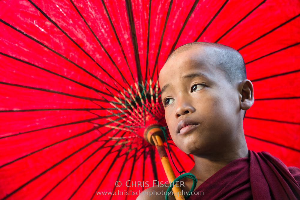 A young novice monk with a red parasol in Mandalay, Myanmar.