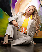 Fashion model Brenna Smith poses in a khaki men's dress suit in front of an abstract art backgound.  Photo by Gerard Harrison Image Theory Photoworks