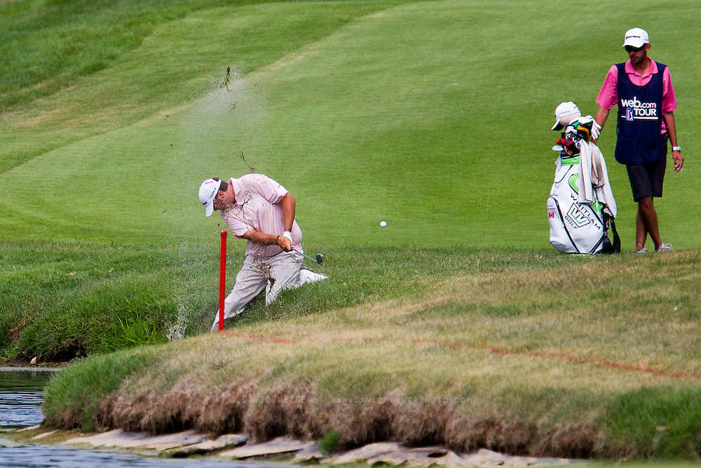 Stuart Anderson hits out of the shallow water off the 18th hole during the final round of the 2012 Price Cutter Charity Championship at Highland Springs Country Club on August 12, 2012 in Springfield, Missouri. (David Welker/www.TurfImages.com).
