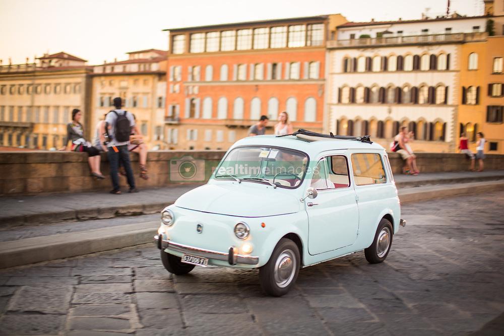 Pastel blue Fiat crossing Ponte Santa Trinita bridge, Florence, Italy. 28/08/15. Photo by Andrew Tallon
