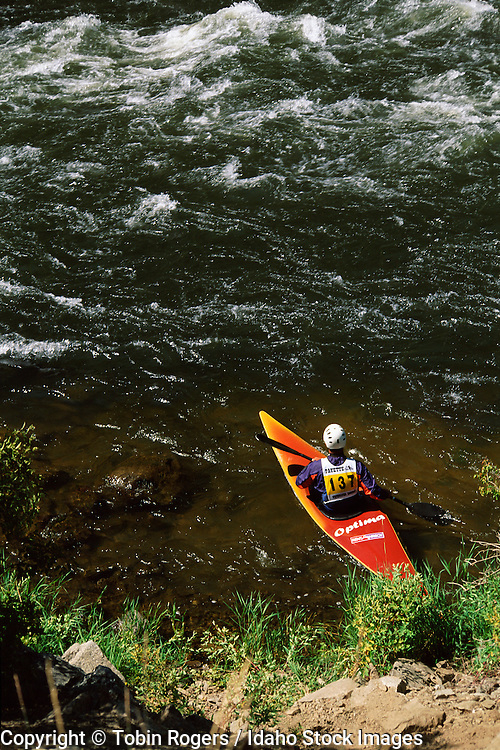 IDAHO. Banks. North Fork of Payette River. Male kayaker prepares to enter whitewater at a race through Otter Slide rapid on summer morning.