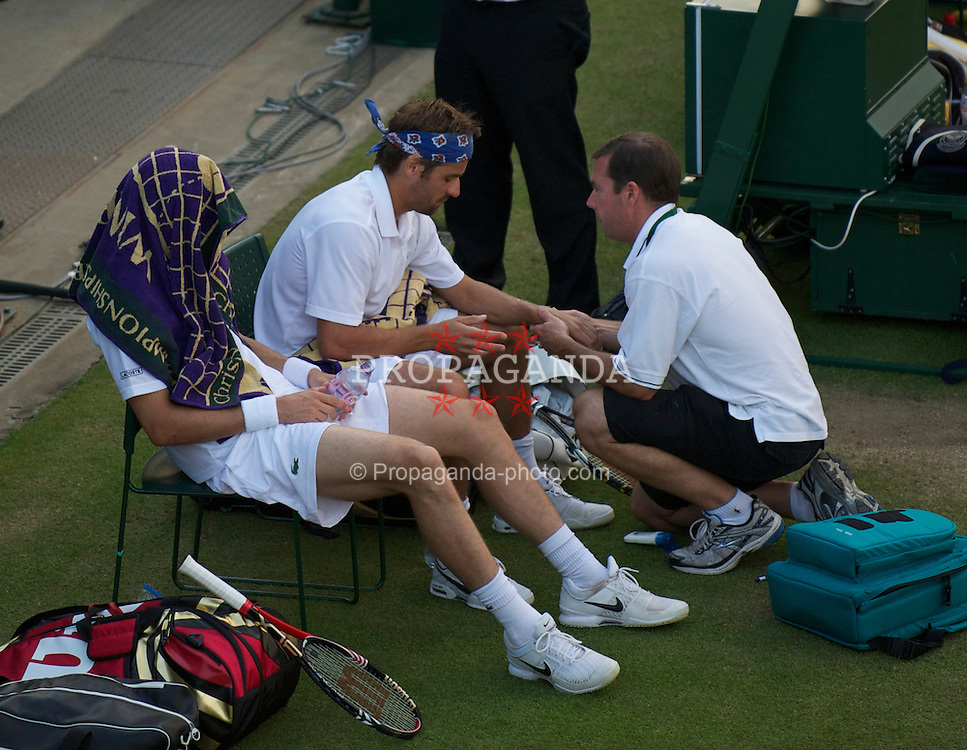 LONDON, ENGLAND - Thursday, June 24, 2010: Arnaud Clement (FRA) receives treatment for a wrist injury during the Gentlemen's Doubles 1st Round match on day four of the Wimbledon Lawn Tennis Championships at the All England Lawn Tennis and Croquet Club. (Pic by David Rawcliffe/Propaganda)
