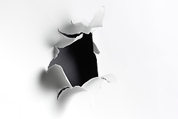 Explosive torn hole in white paper background