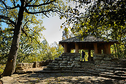 A hiker cools off in the shade of shelter built by the Civilian Conservation Corps (CCC) in Devil's Den State Park. The shelter provides easy access to views overlooking  the Lee Creek Valley.<br /> <br /> Devil's Den State Park is an Arkansas state park located in the Lee Creek Valley of the Boston Mountains in the Ozarks. Devil's Den State Park contains one of the largest sandstone crevice areas in the U.S. The park contains many geologic features such like crevices, caves, rock shelters, and bluffs. The park is also known for its well-preserved Civilian Conservation Corps (CCC) structures built in the 1930s. These structures, still in use today include cabins, trails, a dam, and shelter.<br /> <br /> Devil's Den State Park has approximately 64 miles of trails that are popular with hikers, mountain bikers and horseback riders. One popular trail is the Devil's Den Self-Guided Trail (1.5 miles long) that passes by Devil's Den Cave (550 feet), Devil's Den Ice Box, numerous rock crevices, and Twin Falls. Another popular trail is the Yellow Rock Trail (3.1 miles) that leads to expansive views of the Lee Creek Valley.